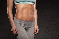 La mujer femenina de la aptitud con el cuerpo muscular, hace su entrenamiento, ABS, abdominals Foto de archivo libre de regalías