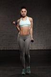 La mujer femenina de la aptitud con el cuerpo muscular, hace su entrenamiento con pesas de gimnasia Foto de archivo libre de regalías