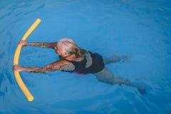 La mujer femenina mayor se aferra a un dispositivo de flotación en una piscina para aprender cómo nadar imagen de archivo libre de regalías
