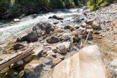La mujer femenina que se sienta en las aguas termales naturales utiliza sus brazos para mezclar la agua caliente y fría para regu imagenes de archivo