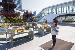 La mujer fiel budista ruega el centro comercial exterior de MBK, en Bangkok, Tailandia fotografía de archivo libre de regalías