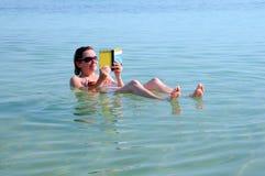 La mujer flota en el mar muerto Fotos de archivo