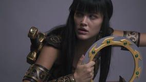 La mujer formidable del Amazonas en armadura del oro sostiene el arma y mira alrededor, cámara lenta metrajes