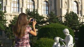 La mujer fotografía la escultura en el teléfono almacen de video