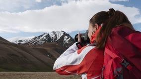 La mujer fotografía los picos de montaña almacen de video
