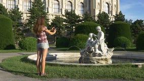 La mujer fotografía una estatua en un teléfono móvil almacen de video
