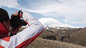 La mujer fotografía una montaña nevosa almacen de metraje de vídeo