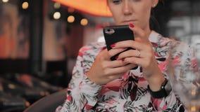 La mujer francesa femenina joven desconocida utiliza un smartphone mientras que se sienta en un restaurante En la mano es un relo metrajes