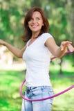 La mujer gira el aro del hula afuera Imagen de archivo libre de regalías