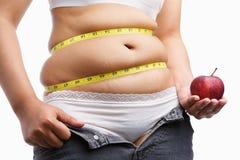 La mujer gorda con desabrocha los pantalones vaqueros que sostienen la manzana Imagen de archivo