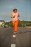 La mujer gorda joven hermosa está corriendo Fotos de archivo libres de regalías