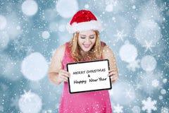 La mujer gorda lleva a cabo al tablero del saludo para el día de la Navidad Imágenes de archivo libres de regalías