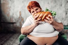 La mujer gorda se sienta en silla y come el bocadillo, bulímico imagen de archivo