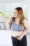 La mujer gorda sostiene la manzana en cocina Imágenes de archivo libres de regalías