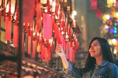 La mujer goz? el mirar de las l?mparas rojas y de los deseos en templo chino fotografía de archivo