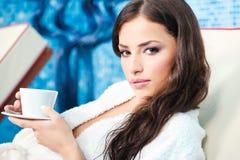 La mujer goza de la taza de café en centro del balneario Imagenes de archivo