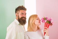 La mujer goza de las flores del ramo de la fragancia Los pares en el amor feliz celebran aniversario La señora le gusta el marido foto de archivo libre de regalías