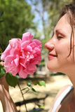 La mujer goza de un olor de un rosado se levantó imágenes de archivo libres de regalías