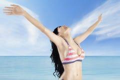 La mujer goza del aire fresco en la costa Imagen de archivo libre de regalías