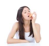 La mujer goza del buñuelo dulce. Comida basura malsana Imágenes de archivo libres de regalías
