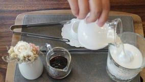 La mujer goza del café hecho a mano de la leche helada del arte almacen de video
