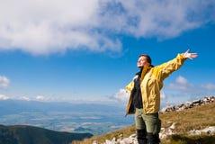 La mujer goza del sol en montañas en ir de excursión Fotografía de archivo