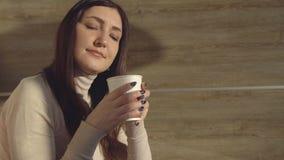 La mujer goza el beber del café fresco caliente de una taza de papel almacen de video