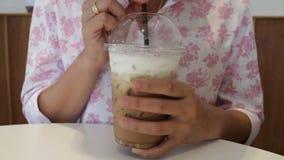 La mujer goza el beber del café helado del capuchino almacen de metraje de vídeo