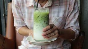 La mujer goza el beber del latte helado del té verde almacen de metraje de vídeo