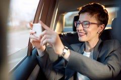 La mujer goza en las fotos que viajan y que toman de un coche Fotos de archivo