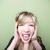 La mujer grita con los oídos cubiertos Imagen de archivo libre de regalías