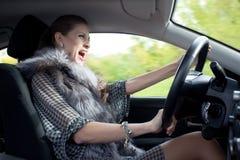La mujer grita en coche Foto de archivo libre de regalías