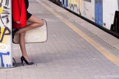 La mujer guarda el equipaje en el subterráneo Imagenes de archivo