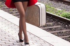 La mujer guarda el equipaje en la plataforma del tren Foto de archivo