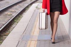 La mujer guarda el equipaje en la plataforma del tren Fotos de archivo
