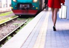 La mujer guarda el equipaje en la plataforma del tren Fotografía de archivo