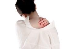 La mujer ha dolido en la parte posterior y el cuello en el fondo blanco Foto de archivo