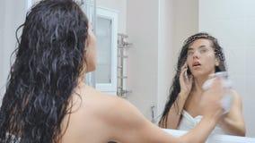 La mujer habla en el teléfono después de ducha delante del espejo en cuarto de baño metrajes