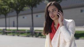 La mujer habla en el teléfono que se sienta afuera metrajes