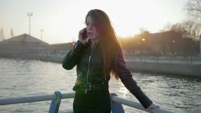 La mujer habla en smartphone, desarrolla el pelo en el contraluz, teléfono móvil a disposición de la mujer joven, conversación so almacen de metraje de vídeo