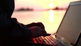 La mujer habla en un ordenador portátil en la playa almacen de video