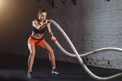 La mujer hace ejercicio con la cuerda de la batalla en gimnasio funcional del entrenamiento fotos de archivo libres de regalías