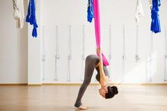 La mujer hace ejercicios aéreos de la yoga, se inclina con las piernas rectas Foto de archivo libre de regalías