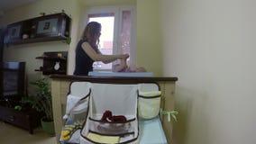 La mujer hace el masaje para el bebé de 5 meses en sala de estar 4K almacen de video