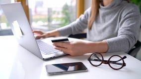 La mujer hace el pago en línea en casa con una tarjeta de crédito y un ordenador portátil metrajes