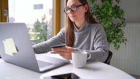 La mujer hace el pago en línea en casa con una tarjeta de crédito y un ordenador portátil almacen de video
