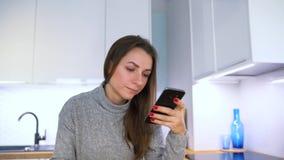 La mujer hace el pago en línea en casa con una tarjeta y un smartphone de crédito almacen de video