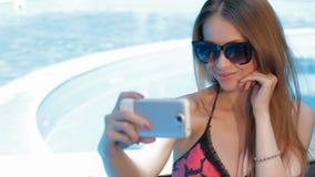 La mujer hace el selfie cerca de la piscina almacen de metraje de vídeo