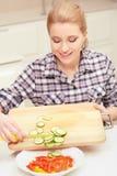 La mujer hace la ensalada de verduras frescas imagenes de archivo