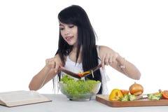 La mujer hace la ensalada mientras que libro de lectura Imagenes de archivo